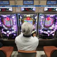 Concentration exercises: A visitor plays pachinko at a parlor in Koga, Ibaraki Prefecture, in April. | REUTERS