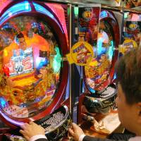 A player turns a dial on the right to try to control the trajectory of the balls so that they fall into winning pockets in the board. Each ball that lands in a winning pocket earns about 10 more balls and starts the digital slot machine in the center of the board. | BLOOMBERG