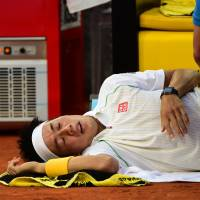 Valiant effort: Kei Nishikori receives treatment from a trainer during the final of the Madrid Open against Rafael Nadal on Sunday. Nishikori retired with a hip injury in the third set. | AFP-JIJI