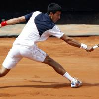 Superb: Novak Djokovic plays a shot from Milos Raonic in their semifinal match at the Rome Masters on Saturday. | REUTERS