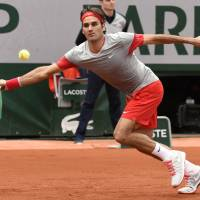 Easy does it: Roger Federer attempts to hit a return against Lukas Lacko during their first-round match at the French Open on Sunday. Federer won 6-2. 6-4, 6-2.   AFP-JIJI
