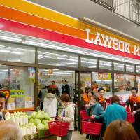 Customers shop at a newly opened Lawson Mart in Osaka last month. | KYODO