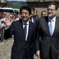 Prime Minister Shinzo Abe waves as he arrives with Spanish counterpart Mariano Rajoy at the city of Santiago de Compostela on Sunday. | AP