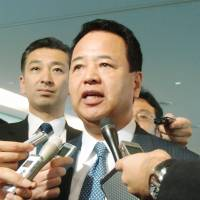 Akira Amari, the minister in charge of the Trans-Pacific Partnership negotiations, responds to reporters at Haneda Airport in Tokyo on Monday. | KYODO