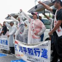 People rally outside U.S. Marine Corps Air Station Futenma in Ginowan, Okinawa Prefecture, on Sunday, to protest the government's plan to shift it further north to less-crowded Nago. | KYODO