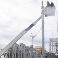 Workers at the Hamaoka nuclear power station in Omaezaki, Shizuoka Prefecture, set up a makeshift utility pole during a disaster drill on Wednesday. | KYODO