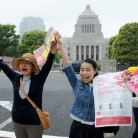 Outside the Diet building Tuesday, activists form a human chain in solidarity against Prime Minister Shinzo Abe's shortcut plan to reinterpret the Constitution to allow Japan to legally exercise the right to collective self-defense. | SATOKO KAWASAKI