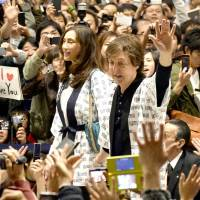Former Beatle Paul McCartney is swarmed by fans as he arrives at Kansai International Airport in Osaka in November 2013. | KYODO