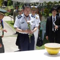 Gen. Shigeru Iwasaki, chief of staff at the Self-Defense Forces Joint Staff Office, prays in front of the grave for fallen soldiers during his visit to the Japanese war cemetery at Yayway, on the outskirts of Yangon, on Wednesday. | AP