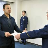 Anuj Raj Karki, a Nepalese resident of Tokyo, receives a letter of appreciation Friday at Kojimachi Police Station in Chiyoda Ward, Tokyo, for rescuing a woman who was nearly run over by a train earlier this month. | KYODO