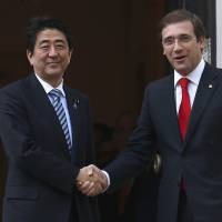 Prime Minister Shinzo Abe is welcomed by his Portuguese counterpart, Pedro Passos Coelho, in Lisbon on Friday. | REUTERS