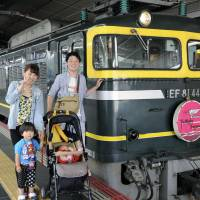 A family has their photo taken Wednesday in JR Osaka Station in front of the Twilight Express sleeper train, which is expected to be retired next spring. | KYODO