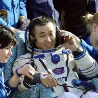 Astronaut Koichi Wakata speaks on a telephone shortly after touchdown aboard a Soyuz re-entry capsule in Kazakhstan Wednesday. He completed a six-month mission aboard the International Space Station and served for several weeks as its commander, becoming the first Japanese in the role. | KYODO