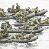 Ground Self-Defense Force personnel approach Eniyabanare Island in Kagoshima Prefecture in dinghies Thursday during a drill simulating the recapture of a remote island.  | KYODO