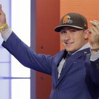 He's money: Quarterback Johnny Manziel gestures to the crowd as he makes his way across the stage after being drafted by the Cleveland Browns on Thursday in New York. | AP