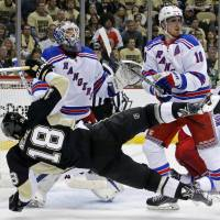 Down in front: The Rangers' Marc Staal (right) knocks down the Penguins' James Neal in front of New York goalie Henrik Lundqvist during Game 1 of their second-round playoff series on Friday. The Rangers won 3-2. | AP