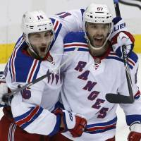 Live to fight another day: Rangers teammates Derick Brassard (left) and Benoit Pouliot celebrate Brassard's goal against the Penguins.   AP