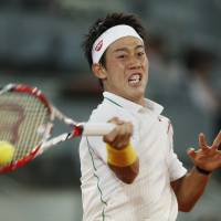 Climbing the ladder: Kei Nishikori hits a return against Feliciano Lopez during their quarterfinal match at the Madrid Open on Friday. Nishikori won 6-4, 6-4 to reach the semifinal round. | AP