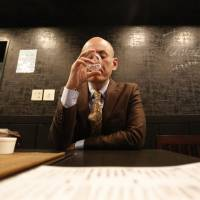 Shiro Fukai has a drink in Otasuke, a pub in Tokyo, on Thursday. | REUTERS