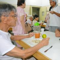 Masayoshi Ibusuki (right), the head of a nursing home for elderly Japanese-Brazilians, speaks with a resident of the home near the port of Santos, in Sao Paulo state, on March 21. | KYODO