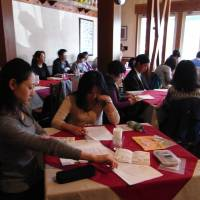 Attendants browse handouts on the Constitution during a 'Constitution cafe' session at a restaurant in Zama, Kanagawa Prefecture, on April 17. The events held by lawyer Keiko Ota are raising general interest in constitutional issues. | MIZUHO AOKI