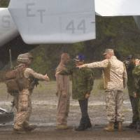 Ryota Takeda (center), parliamentary vice minister for defense, greets a U.S. Marine Corps officer during a joint exercise involving U.S. Marines and the Ground Self-Defense Force at the Aibano Training Area in Takashima, Shiga Prefecture, last Oct. 16. U.S. MV-22 Osprey aircraft also took part in the event. | KYODO