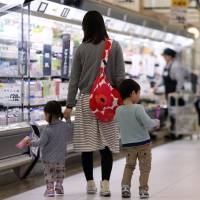 A mother shops with her children in Chiba Prefecture on April 1. The government says it is serious about getting women into the workforce, and is mulling some tax reforms to spur that. | BLOOMBERG