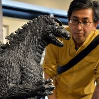 A Godzilla fan checks out a 1-meter tall statue of the famed monster at a dedicated art exhibition in Tokyo on Friday. | AFP-JIJI