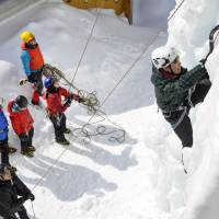 While others watch from below, a person scales an artificial ice wall at the Akadake Kosen hot-spring area in Chino, Nagano Prefecture, in March.   KYODO