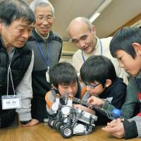 Hiroshi Ishida (left) and other seniors teach young boys about the mechanics of robots in Kashiwa, Chiba Prefecture, in February.  | KYODO