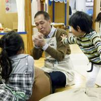 Shinji Kurita takes care of children in Minato Ward, Tokyo, in March. | KYODO