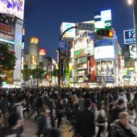 People crossing from every direction flood the main intersection in front of JR Shibuya Station at night. | SATOKO KAWASAKI