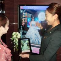 A staffer at a wedding dress rental shop in Tokyo uses a tablet to help a customer select a dress. | KYODO
