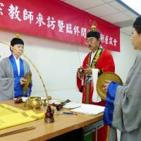 A man and two women chant and play traditional percussion instruments, demonstrating a Taoist ritual for a dying patient at Fu Jen Catholic University in New Taipei City on March 28. | KYODO