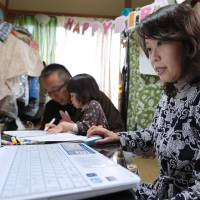 Yuko Nagai uses her computer while her husband, Kazunori, plays with their child, Miku, in their home in Tokyo in March. Prime Minister Shinzo Abe is considering granting entry to more foreign household workers to help women get back to work after giving birth. | BLOOMBERG