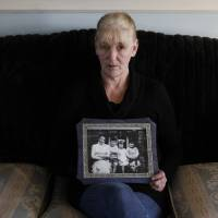 Helen McKendry, shown in January 2012 at her home in Killyleagh, Northern Ireland, holds a family photo showing her with her mother, Jean McConville, and some of her siblings in 1972 before her mother was murdered. | AP