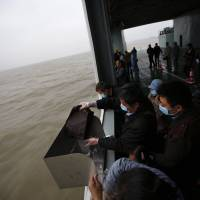 A man scatters the ashes of his parents and grandmother into the ocean during a burial ceremony off Shanghai on May 10. Faced with an aging population, soaring property prices and increasingly scarce land, the Chinese government has been trying for years to convince more people to break with tradition and bury loved ones at sea.   REUTERS