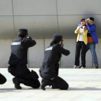 Police officers aim their weapons at a man playing the role of an attacker holding a woman hostage during an anti-terrorism drill at a railway station in Zhengzhou, China, on Wednesday. | REUTERS