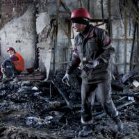 Workers clear away debris from a government building in Mariupol, the second-largest city in Ukraine's eastern Donetsk region, on Friday after steelworkers forced pro-Russia insurgents to retreat from buildings they had seized. | AP