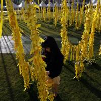 A woman ties a yellow ribbon to commemorate the dead passengers onboard the sunken ferry Sewol at Seoul City Hall Plaza on Thursday. | REUTERS