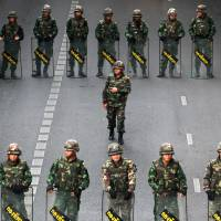 Thai soldiers stand guard to prevent a rally in Bangkok on Thursday.