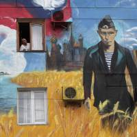 Recent graffiti on a residential building in Sevastopol, Crimea, depicting the Kremlin, Russian President Vladimir Putin and the Russian flag. Moscow calls the peninsula sovereign Russian territory, a claim unrecognized elsewhere. | REUTERS