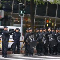 Policemen in riot gear block a street leading to the site of a terrorist attack in downtown Urumqi, the capital of the Xinjiang region, on Friday. | REUTERS