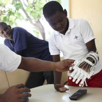 Handicapped Haitian boy Stevenson Joseph (right) learns to use a 3-D printed prosthetic hand at the orphanage where he lives in Santo, near Port-au-Prince, April 28, 2014. | REUTERS