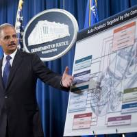 U.S. Attorney General Eric Holder points to an illustration of auto parts during a news conference at the Justice Department in Washington last September. A federal investigation into price-fixing in the auto parts industry has become the largest antitrust investigation in Justice Department history. | AP