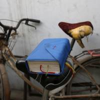 A Bible balances on a bicycle saddle outside an underground Catholic church in the northern Chinese city of Tianjin on Nov. 10. | REUTERS