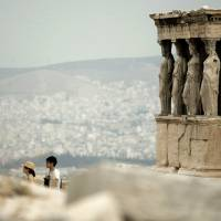 Tourists walk in front of the caryatid statues at the Erechtheion temple on Acropolis Hill in Athens.   AP
