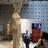 Visitors look at caryatids on show at the Acropolis museum in Athens while a monitor behind  relays the cleaning operation of another caryatid.   AP