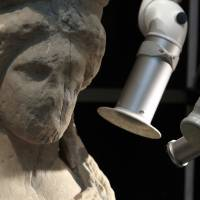 A conservator uses a laser to clean a caryatid at the Acropolis museum in Athens.   AP