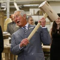 Britain's Prince Charles lifts a wooden mallet while touring a heritage retrofit carpentry exhibit in Charlottetown, Prince Edward Island, Canada, on Tuesday. | REUTERS